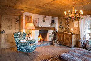 Armchair and wooden trunk next to fireplace in traditional farmhouse