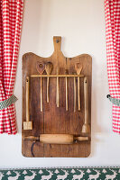 Wooden board repurposed to store kitchen utensils