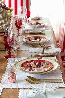 Festliches Gedeck mit Weihnachtswichteln und Goldbesteck