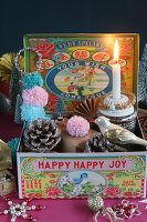Antique Christmas-tree decorations in tin and lit candle