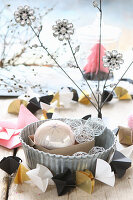 Christmas-tree baubles in cake tin with origami garland