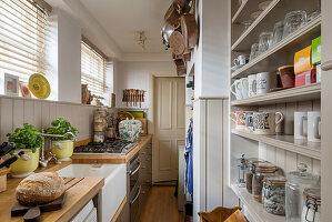 Schmale Küche im Landhausstil mit halbhoher Wandverkleidung