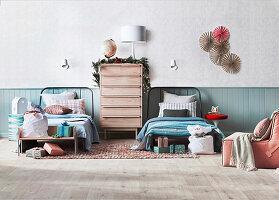 Weihnachtlich dekorierte Kommode zwischen zwei Betten, umgeben von Weihnachtsgeschenken