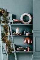 Leiter mit Weihnachtsgirlande vor weihnachtlich dekoriertem Regal