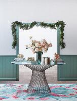 Runder Tisch aus Metall und Glas mit Blumenstrauß und Geschenken vor Durchgang mit Weihnachtsgirlande
