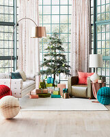 Verpackte Geschenke unter Weihnachtsbaum, Sofa und Sessel im Wohnzimmer mit Glaswänden