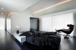 Designer furniture in minimalist, monochrome bedroom; person sitting in lounger