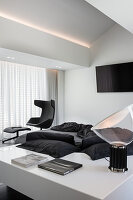 Designer armchair with footstool in monochrome bedroom