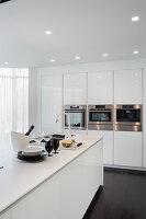 Weiße Desingerküche mit Kochinsel und Einbaugeräten