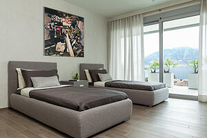 Twin beds with upholstered frames in minimalist grey bedroom