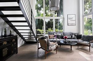 Wohnraum mit hohen Wänden, Sitzecke und Treppe zur Galerie