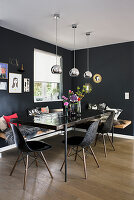 Dining table, classic chairs and modern wooden corner bench in black dining room