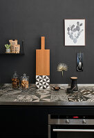 Tiled, black-and-white patterned worksurface in black kitchen