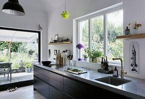 Black kitchen counter in kitchen area with access to terrace
