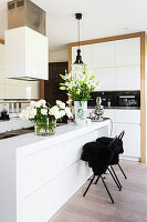 White cabinets and vases of flowers on island counter in modern kitchen