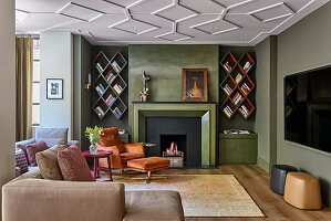 Armchair and footstool next to fireplace and diamond-shaped bookshelves in TV room
