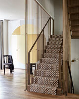 Lattice-patterned carpet on stairs with metal handrail