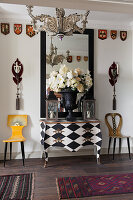 Bombe chest painted with black-and-white diamond pattern flanked by designer chairs