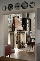 Wooden mantelpiece decorated with pillars, candlesticks and collection of plates
