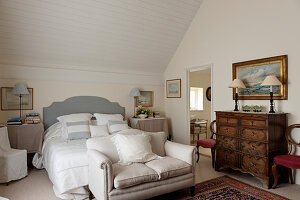 Linen scatter cushions and bedspread in bedroom with antique chest of drawers and small sofa