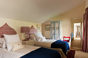 Red paisley patterned linen headboards in twin bedroom with wool and linen blankets and striped lampshade