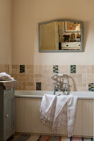 Pale wall tiles and mirror on wall above bath in bathroom