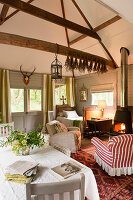 Cosy open plan living in small cottage with woodburning stove and antique armchairs