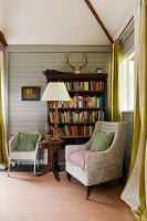 Bookshelf and seating area in cosy open plan cottage