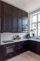 Deckenhohe Einbauküche mit schwarzen Fronten und weißem Metro-Fliesenspiegel
