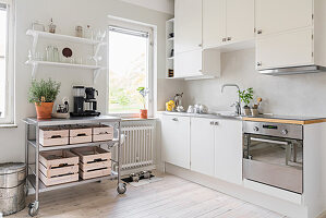 Wooden boxes on trolley in white kitchen
