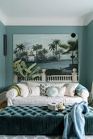 Pale sofa with scatter cushions below large art print and ottoman in foreground in green interior