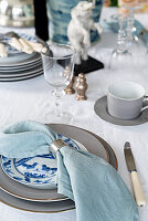 Table setting with blue linen napkin and silver napkin ring