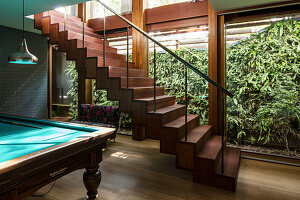 Billiard table next to self-supporting staircase in basement room with windows