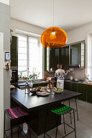 Pendant lamp with orange lampshade above counter and barstools in kitchen and woman in background