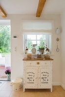 Storage jars on top of shabby-chic cabinet below window