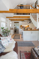 Kitchen in open-plan, double-height interior with exposed wooden beams