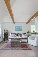 Country-house-style living room with wooden beams in double-height interior