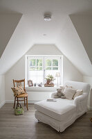 Chaise and wooden chair next to lattice window in gable end wall