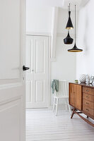Open panelled door leading into white hallway with white wooden floor and wooden sideboard