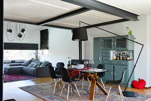 Sofa and dining table in open-plan loft apartment with steel joists