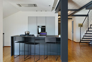 Open-plan kitchen in shades of grey in loft apartment with steel joists