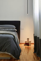 Minimalist ceiling light illuminating stack of books next to bed