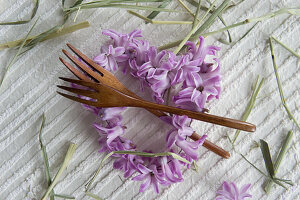 Heart-shaped wreath of hyacinth florets and wooden cutlery