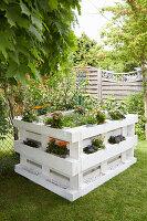 Selbstgebautes Hochbeet aus Paletten mit Blumen im sommerlichen Garten