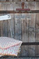 Alter rostfarbener Rechen als Gläserhalter an einer Holztür