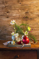 Christmas-tree baubles used as vases for hellebores and white pine branches