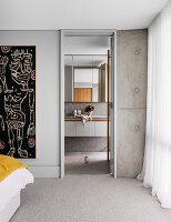 Blick vom Schlafzimmer mit Betonwand ins Bad Ensuite