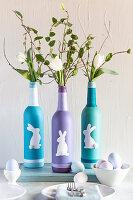 Bemalte und mit Osterhasen dekorierte Flaschen als Vasen