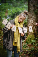Girl hanging up autumn garland in woods