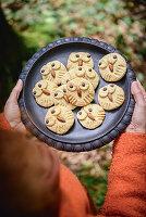 Kekse in Eulenform auf einem schwarzen Teller